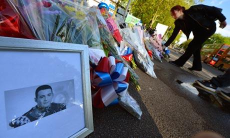 Een foto van Lee Rigby bij de bloemen op de plaats waar hij werd vermoord